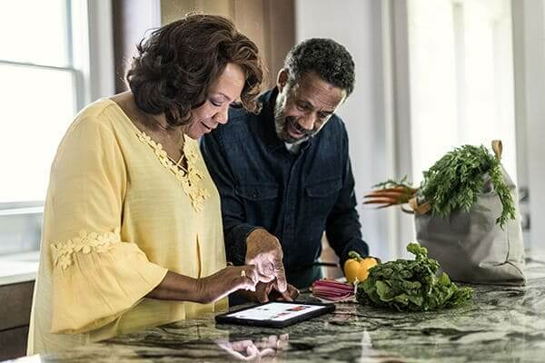 Couple looking at a tablet on the kitchen counter